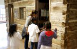 Three children and an adult look into a historic cabin in Heritage Hall